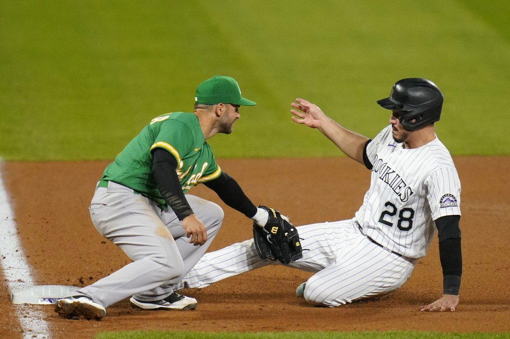 Oakland Athletics third baseman Tommy La Stella tags out Colorado Rockies' Nolan Arenado during the eighth inning of a baseball game, Tuesday, Sept. 1...