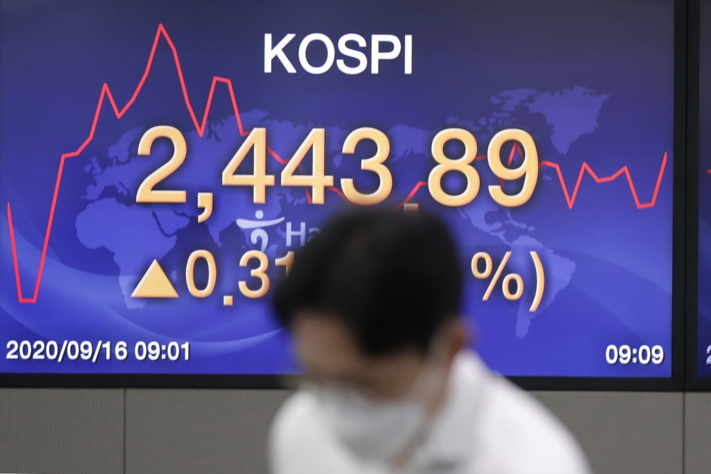A currency trader stands near a screen showing the Korea Composite Stock Price Index (KOSPI) at the foreign exchange dealing room in Seoul, South Kore...