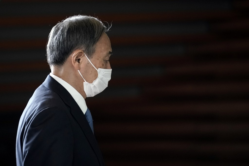 Former Chief Cabinet Secretary Yoshihide Suga walks at the prime minister's office after a cabinet meeting Wednesday, Sept. 16, 2020, in Tokyo. Prime ...