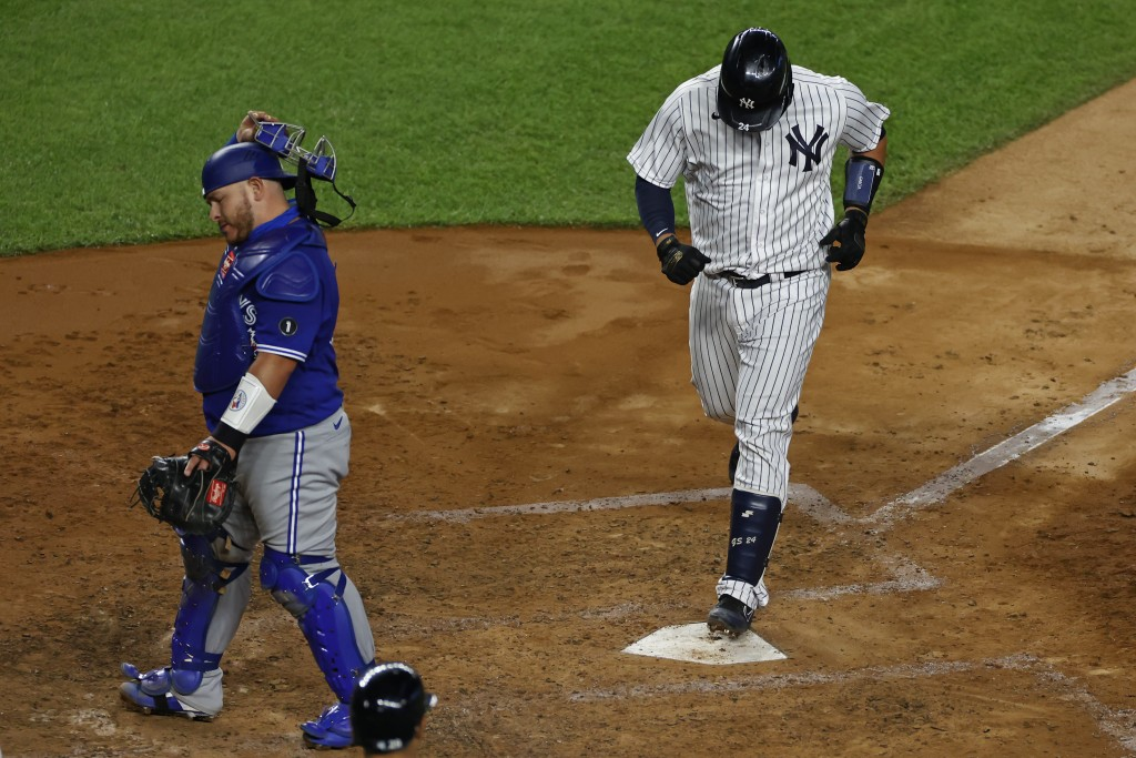 Toronto Blue Jays catcher Alejandro Kirk turns away as New York Yankees' Gary Sanchez steps on home plate after hitting a three-run home run during th...