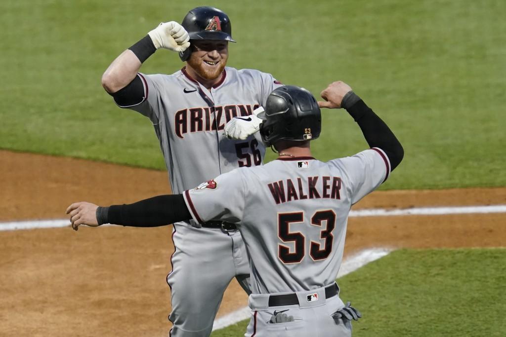 Arizona Diamondbacks' Kole Calhoun, left, celebrates a two-run home run with Christian Walker during the first inning of the team's baseball game agai...