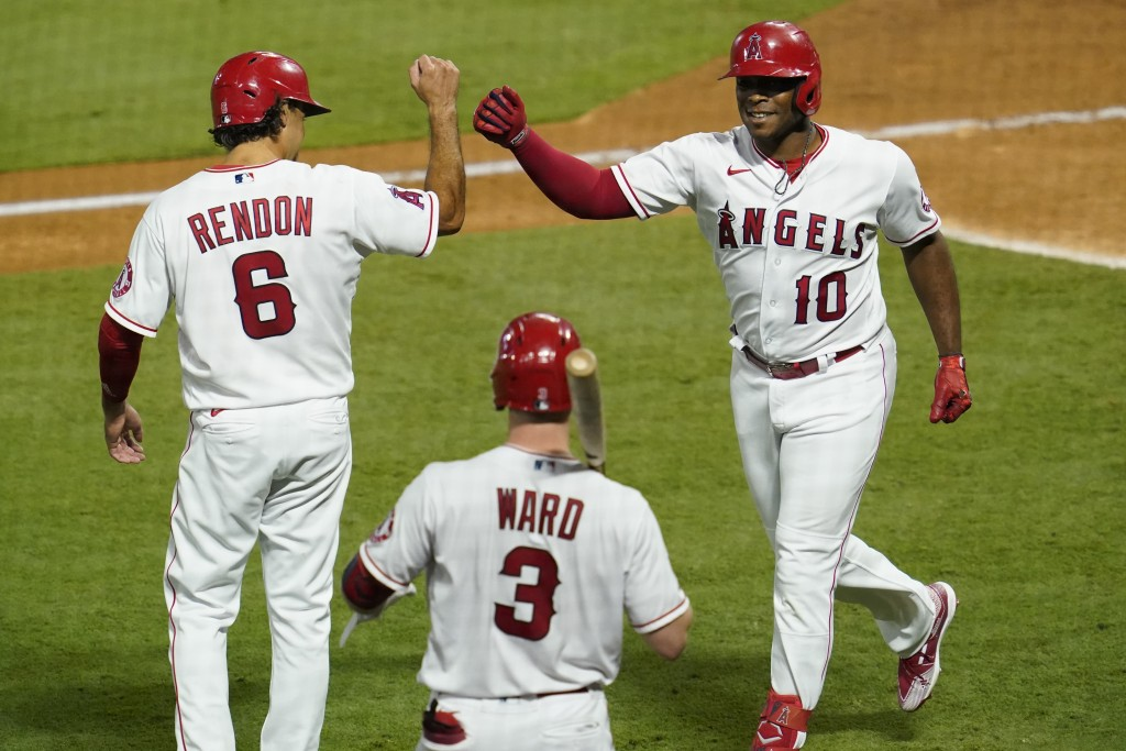 Los Angeles Angels' Justin Upton, right, celebrates his two-run home run with Anthony Rendon, left, and Taylor Ward during the fifth inning of the tea...
