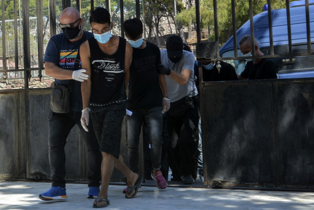 Suspects, all from Afghanistan escorted by plain clothes policemen and wearing face masks, arrive at a court in Mytilene, the capital of the northeast...