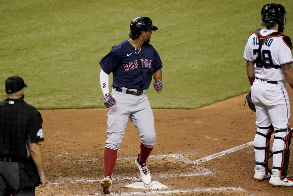 Boston Red Sox's Xander Bogaerts, left scores past Miami Marlins catcher Jorge Alfaro on a double hit by J.D. Martinez during the sixth inning of a ba...