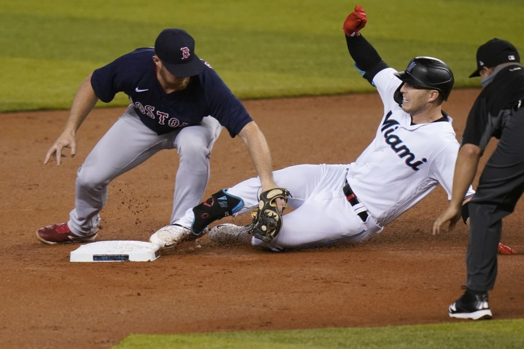 Miami Marlins' Corey Dickerson, right, is tagged out at second by Boston Red Sox third baseman Christian Arroyo, left, during the first inning of a ba...