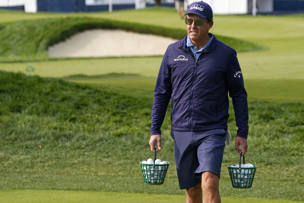 Phil Mickelson carries two buckets of balls as he heads to the range prior to a practice round before the U.S. Open Championship golf tournament, Tues...