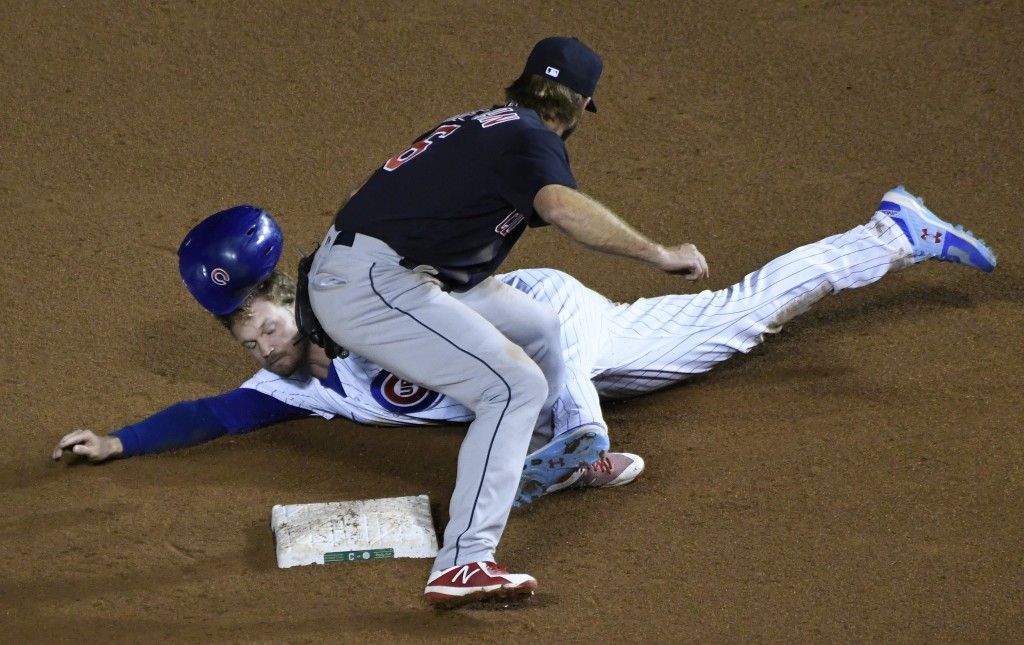 Cleveland Indians second baseman Mike Freeman (6) tags out Chicago Cubs' Ian Happ (8) at second base on a steal attempt during the seventh inning of a...