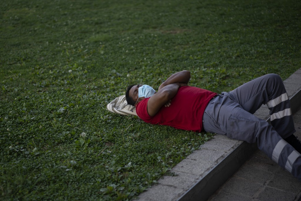 A man wearing a face mask to prevent the spread of coronavirus sleeps in a public park in Barcelona, Spain, Tuesday, Sept. 15, 2020. Spain's official ...