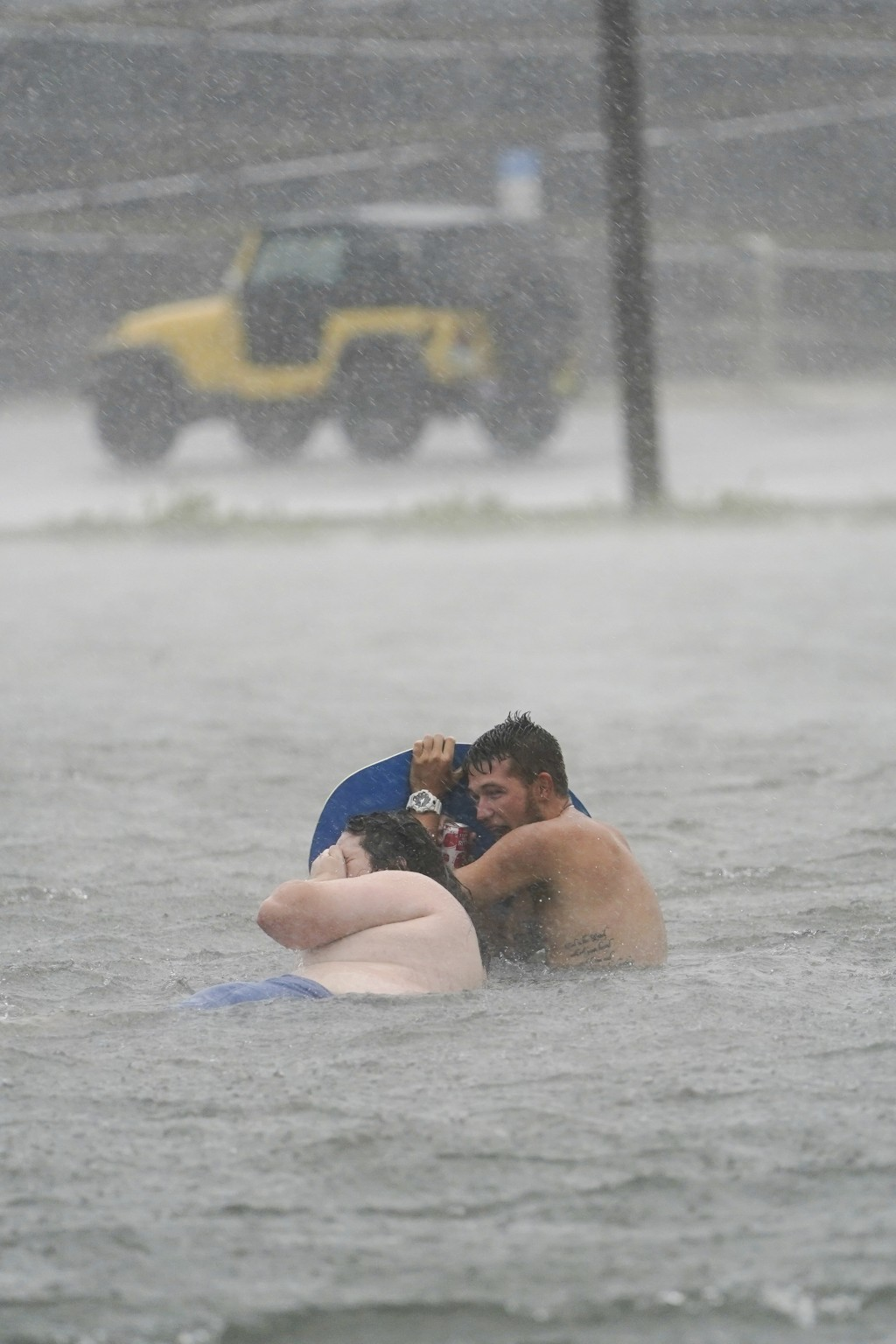 People play in a flooded parking lot at Navarre Beach, Tuesday, Sept. 15, 2020, in Pensacola Beach, Fla. Hurricane Sally is crawling toward the northe...