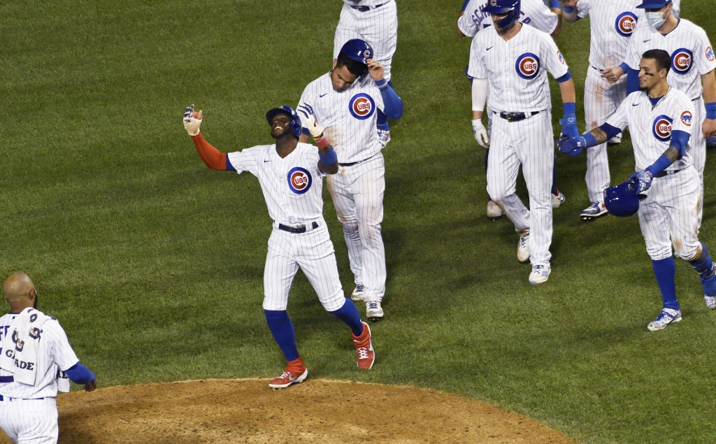 Chicago Cubs' Cameron Maybin, on mound, gestures after walking to force in the the winning run against the Cleveland Indians in a baseball game Tuesda...