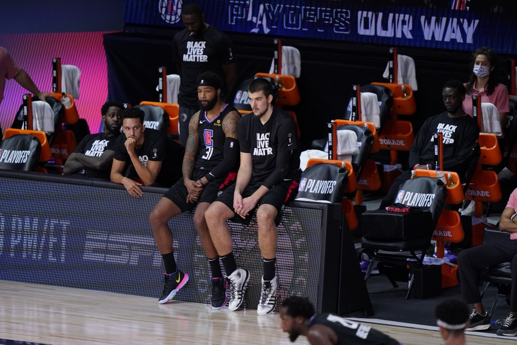 The Los Angeles Clippers players sit on the bench during the second half as they fall to the Denver Nuggets in an NBA conference semifinal playoff bas...