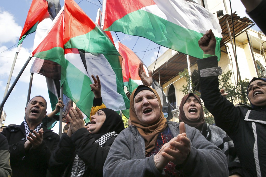 FILE - This Friday, Jan. 31, 2020 file photo, Palestinians chant slogans as they hold Palestinian flags, during a protest against the White House plan...