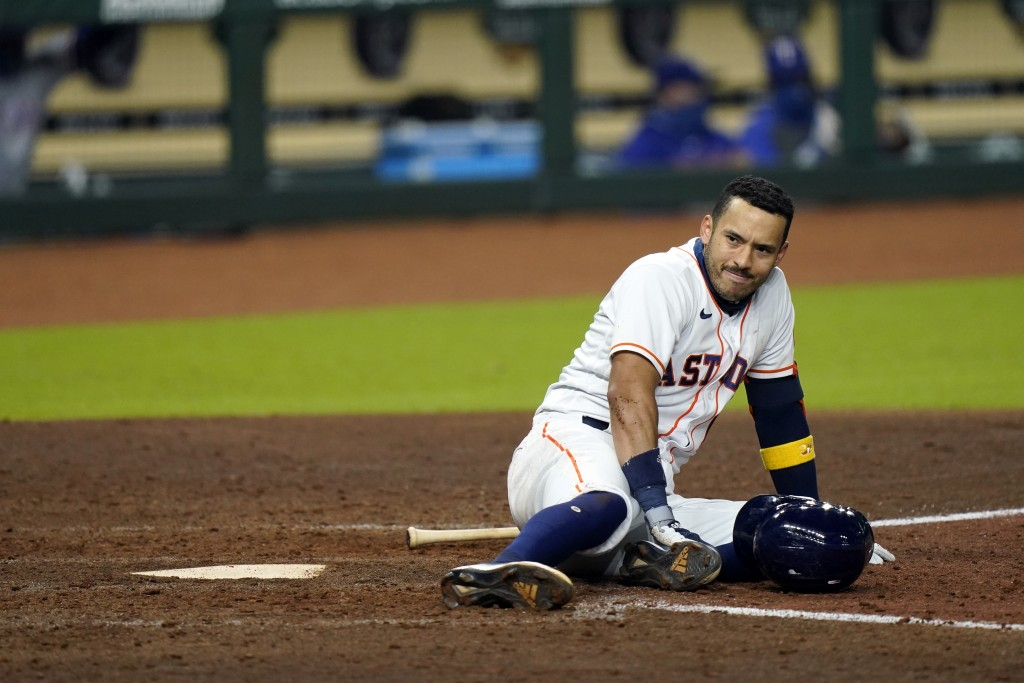 Houston Astros' Carlos Correa waits for medical attention after fouling a pitch off his leg during the sixth inning of a baseball game against the Tex...