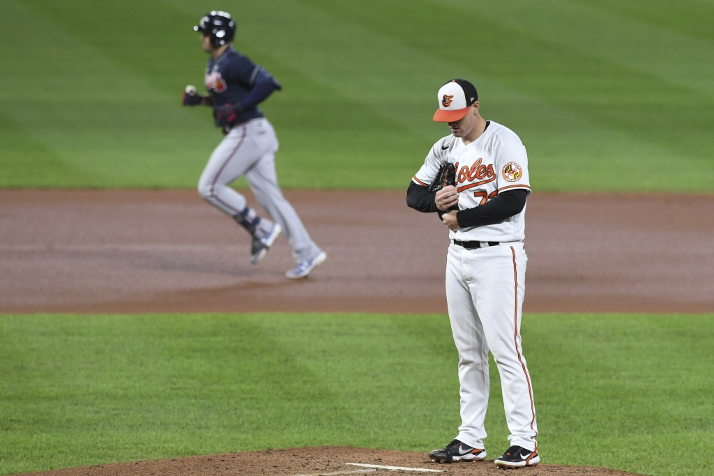 Baltimore Orioles starting pitcher Tom Eshelman, right, reacts to a home run hit by Atlanta Braves left fielder Adam Duvall, left, during the fourth i...