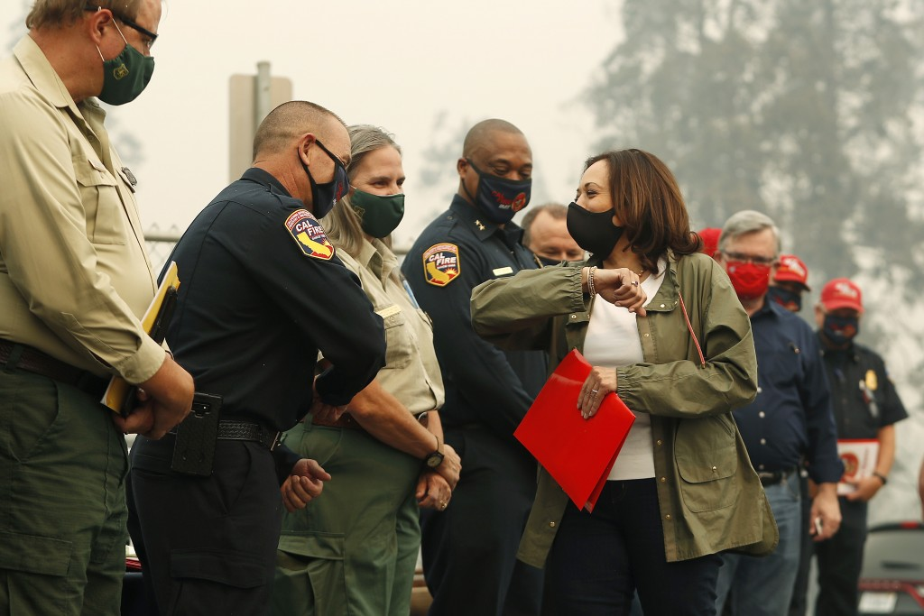 Democratic vice presidential candidate Sen. Kamala Harris, D-Calif., bumps elbows with first responders as she was briefed on the Creek Fire at Pine R...