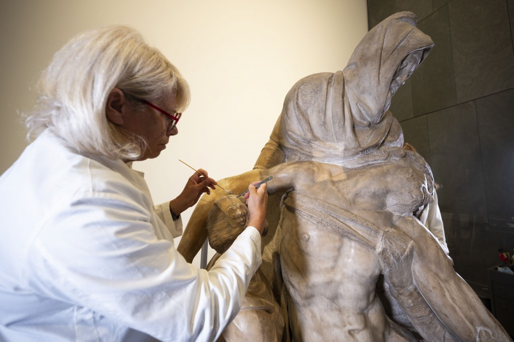 A restorer works on one of Michelangelo's Pieta sculpture in Florence, Italy, Tuesday, Sept. 8, 2020. A restoration of one of Michelangelo's Pieta scu...