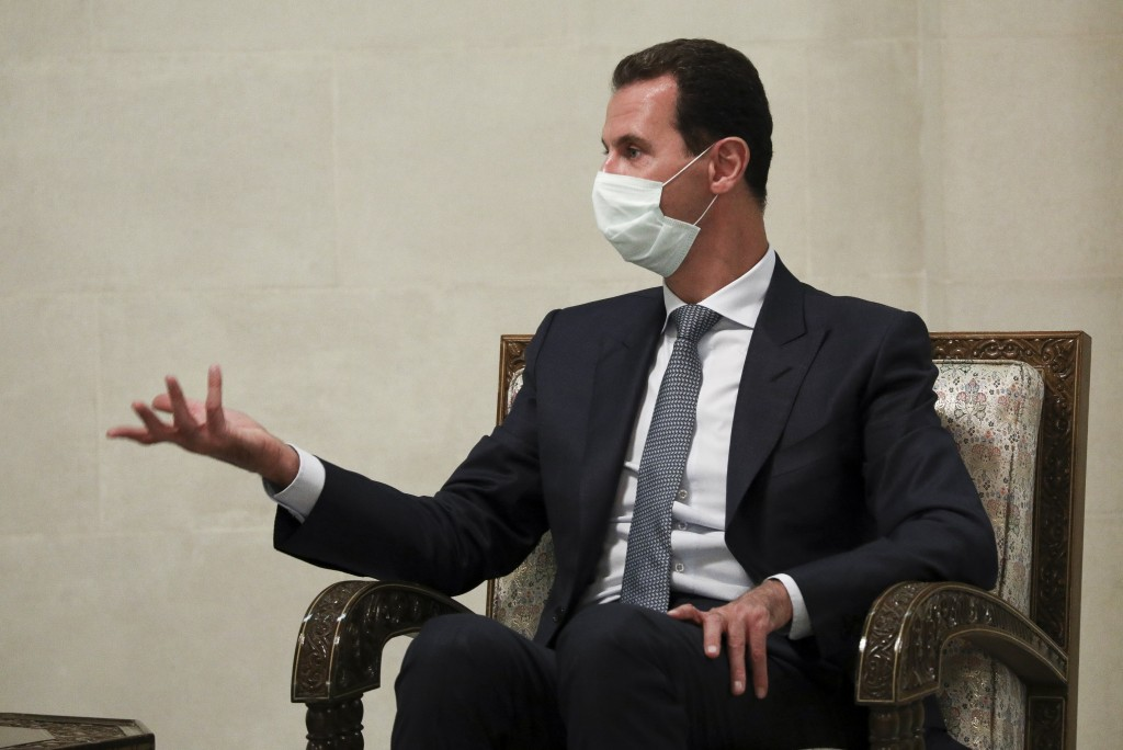 FILE - In this Monday, Sept. 7, 2020 file photo released by Russian Foreign Ministry Press Service, Syrian President Bashar al-Assad gestures while sp...