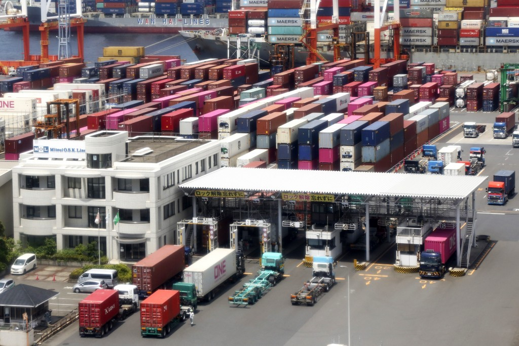 FILE - In this June 17, 2020, file photo, containers are piled up at a port in Yokohama, south of Tokyo. Among the challenges awaiting Prime Minister-...