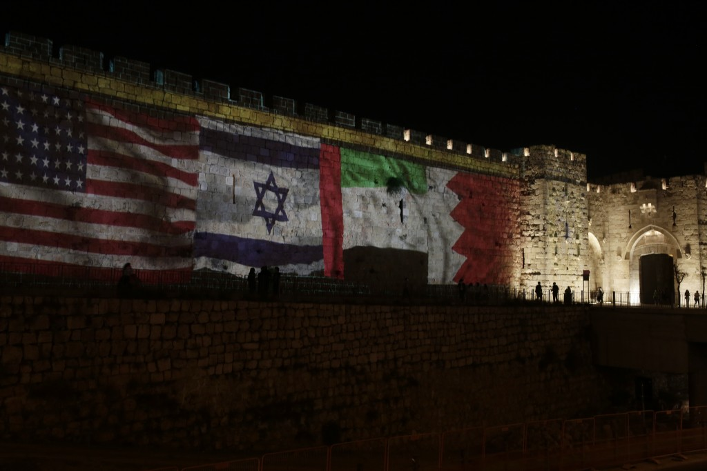 Representations of the U.S., Israeli, Emirati and Bahraini flags are projected onto a wall of Jerusalem's Old City, marking the day of a signing cerem...