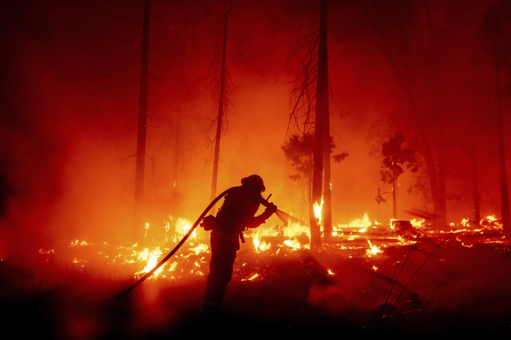 FILE - In this Sept. 7, 2020, file photo, a firefighter battles the Creek Fire as it threatens homes in the Cascadel Woods neighborhood of Madera Coun...