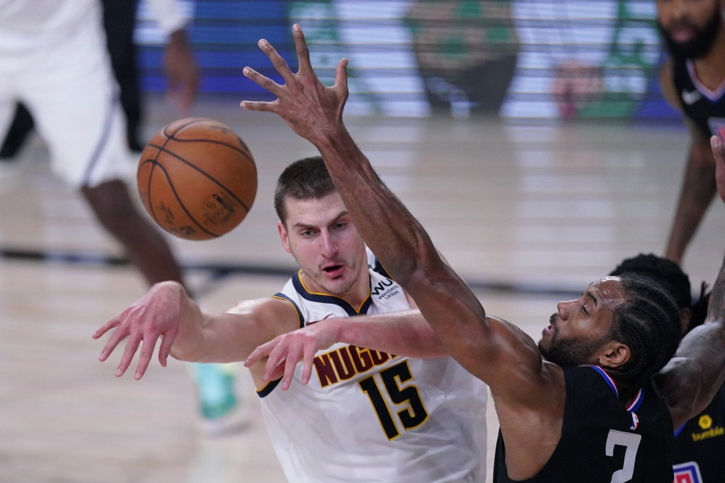 Denver Nuggets center Nikola Jokic (15) passes to ball past Los Angeles Clippers forward Kawhi Leonard (2) during the first half of an NBA conference ...
