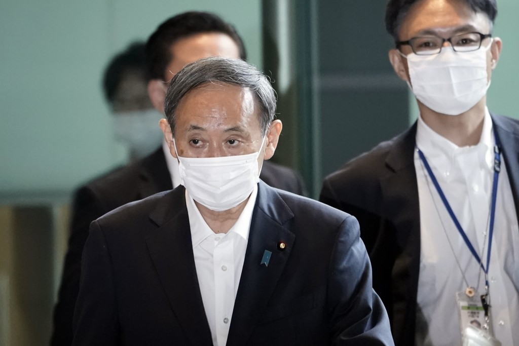 Chief Cabinet Secretary Yoshihide Suga walks in the prime minister's office for a cabinet meeting Wednesday, Sept. 16, 2020, in Tokyo. Japan's incomin...