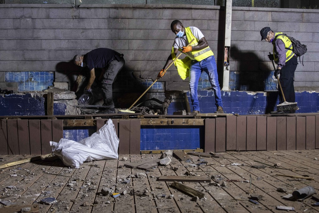 Israeli police inspect the damage at the site hit by a rocket fired by Palestinian militants from the Gaza Strip in the southern city of Ashdod, Israe...