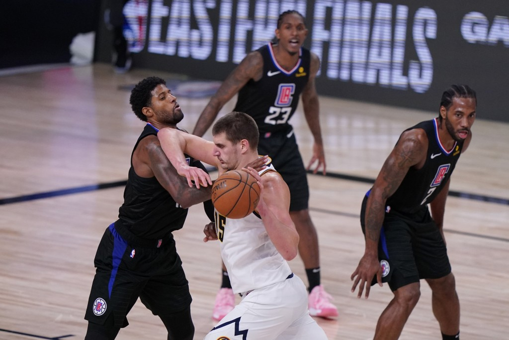 Denver Nuggets center Nikola Jokic (15) drives against Los Angeles Clippers guard Paul George (13) during the second half of an NBA conference semifin...