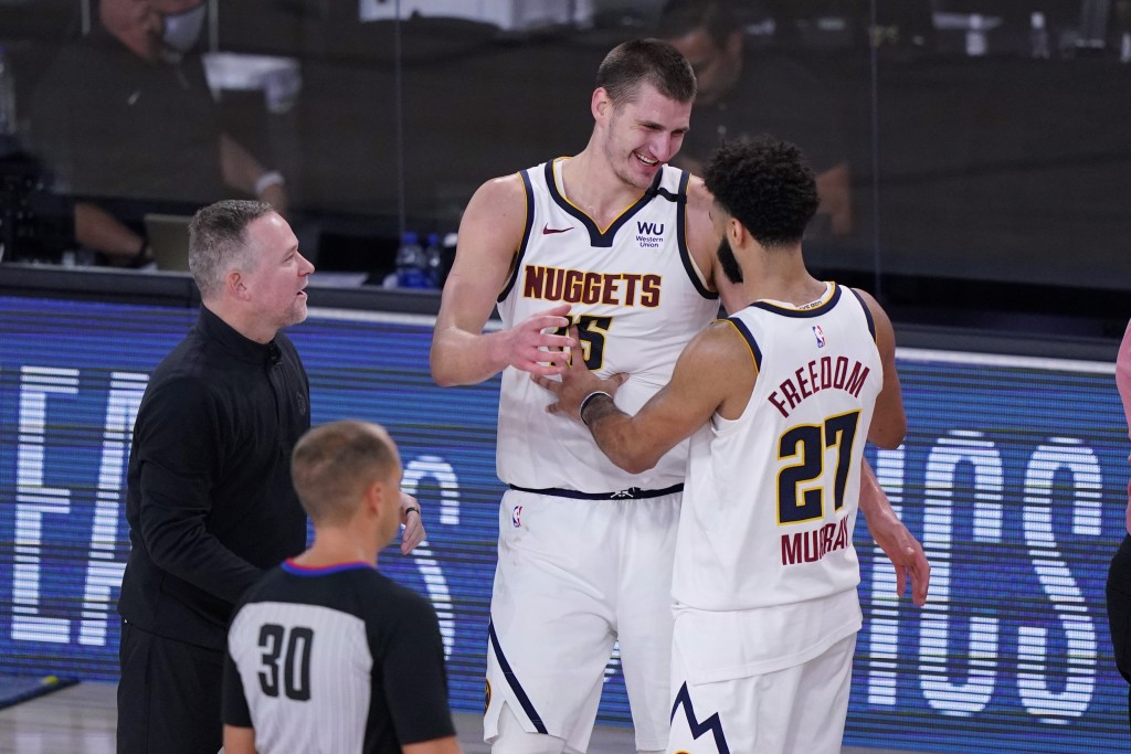 Denver Nuggets head coach Michael Malone, left, celebrates the team's win over the Los Angeles Clippers with center Nikola Jokic (15) and guard Jamal ...