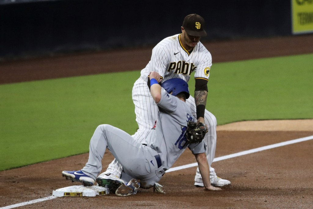 San Diego Padres third baseman Manny Machado applies a tag to Los Angeles Dodgers' Will Smith in the third inning of a baseball game Tuesday, Sept. 15...