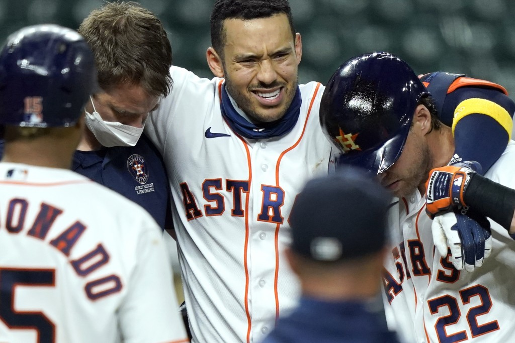 Houston Astros' Carlos Correa, center, is helped off the field after fouling a pitch off his leg during the sixth inning of a baseball game against th...