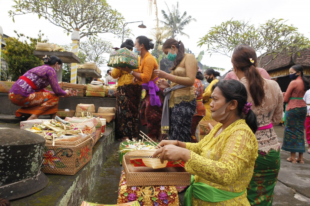 Women wearing face masks as a precaution against the new coronavirus outbreak participate in a Hindu ritual at a temple in Bali, Indonesia, Wednesday,...
