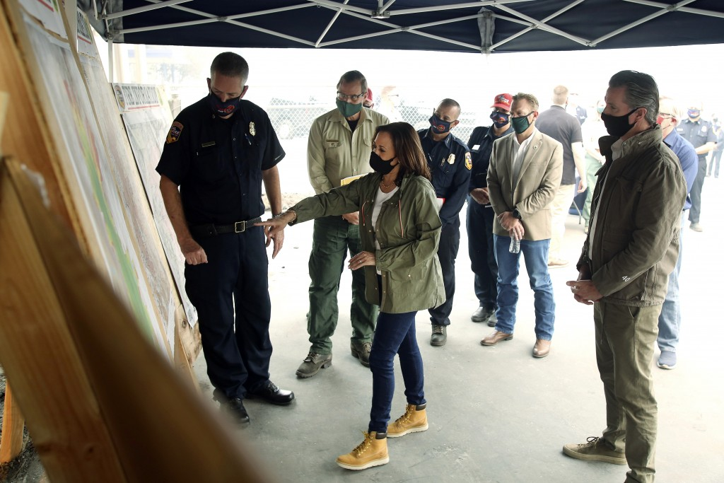 Mark Johnson, left, unit chief for Cal Fire in Fresno, watches Democratic vice presidential candidate Sen. Kamala Harris, D-Calif., and California Gov...