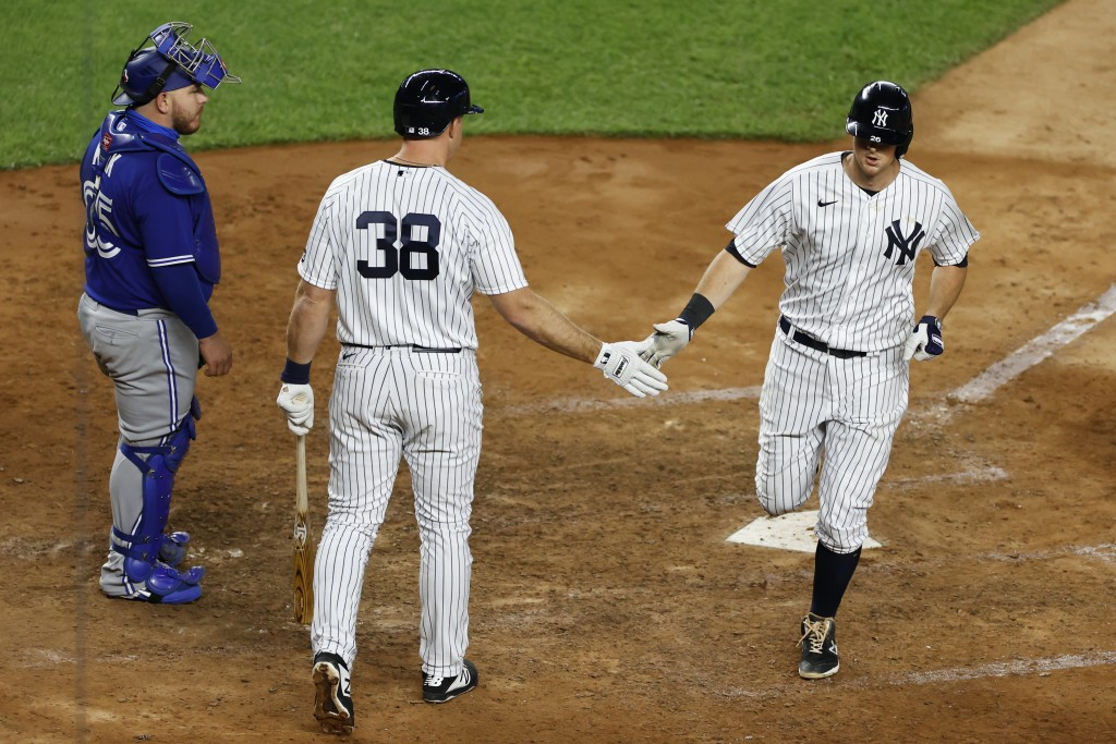 New York Yankees' DJ LeMahieu, right, is congratulated by Erik Kratz, center,  after hitting a solo home run in during the eighth inning of a baseball...