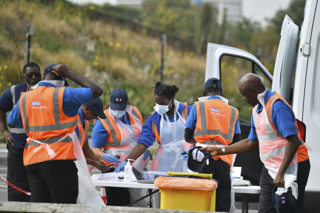 Workers prepare ahead of opening at a Coronavirus testing centre in Southwark, south London, Wednesday, Sept. 16, 2020. The British government plans t...