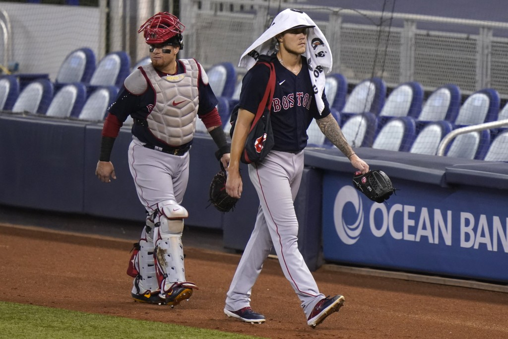 Boston Red Sox catcher Christian Vazquez, left, and starting pitcher Tanner Houck, right, walk to the dugout before a baseball game against the Miami ...