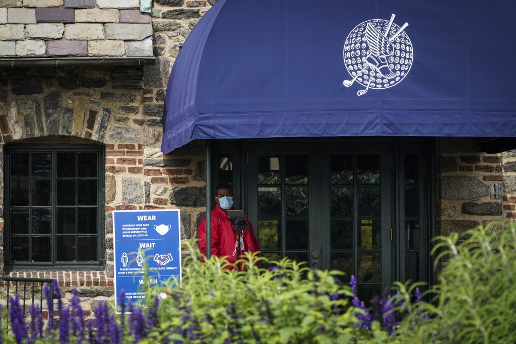 A door attendant wears a protective mask outside the clubhouse on the second day of practices before the U.S. Open Championship golf tournament at Win...