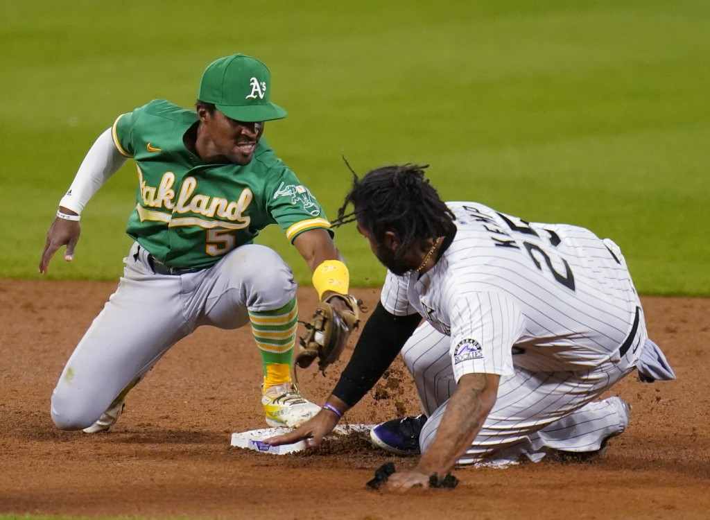 Oakland Athletics' Tony Kemp (5) is late with the tag on Colorado Rockies' Matt Kemp (25) during the sixth inning of a baseball game, Tuesday Sept. 15...