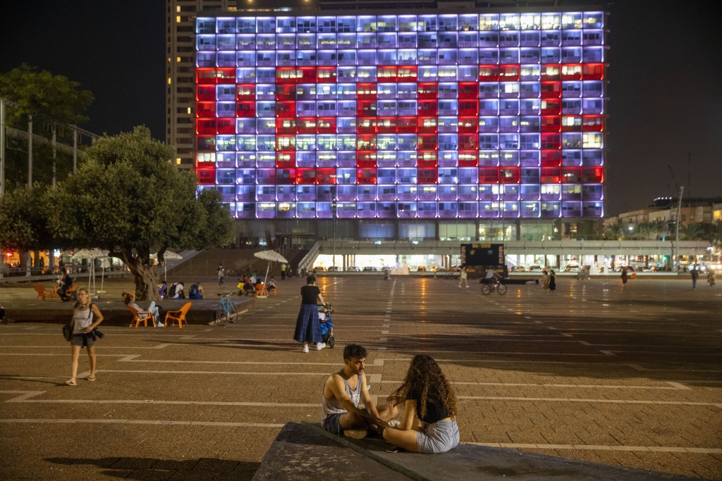 Tel Aviv City Hall is lit up with the words for peace in Hebrew, Arabic and English in honor of the recognition agreements Israel will be signing with...