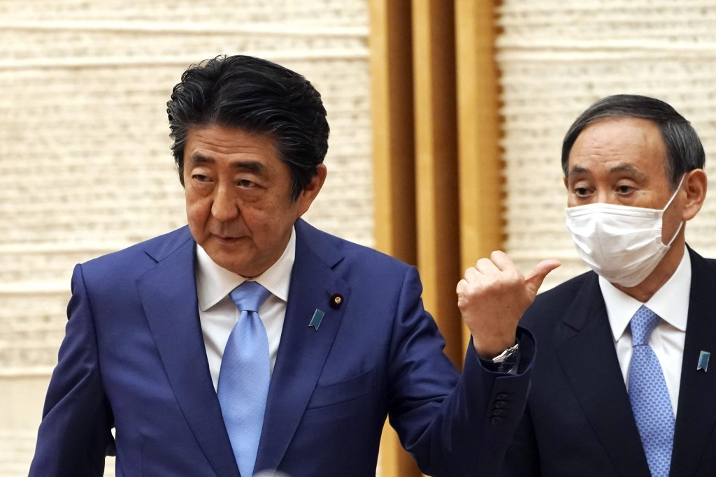 FILE - In this May 4, 2020, file photo, then Japan's Prime Minister Shinzo Abe, left, gestures by then Chief Cabinet Secretary Yoshihide Suga at the e...