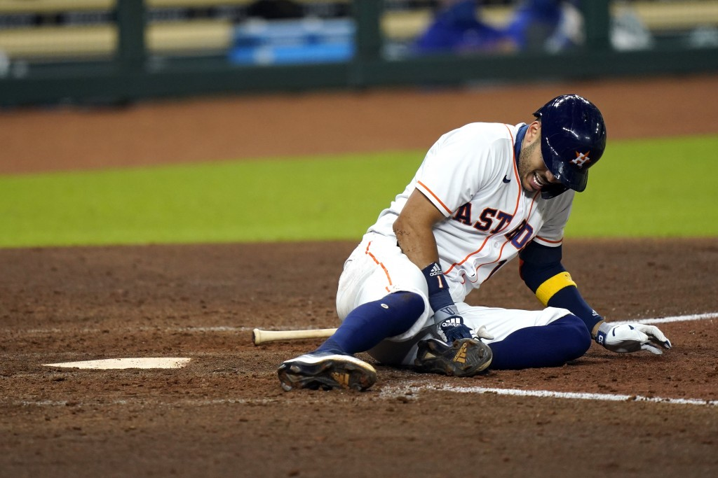 Houston Astros' Carlos Correa reacts after fouling a pitch off his leg during the sixth inning of a baseball game against the Texas Rangers Tuesday, S...