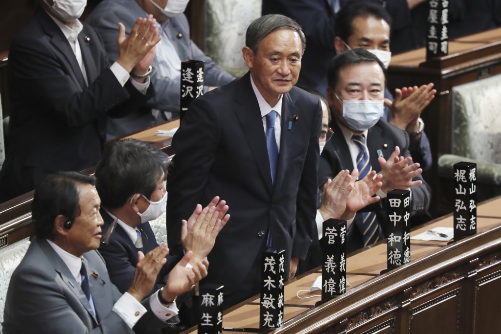 Yoshihide Suga stands up after being elected as Japan's new prime minister at parliament's lower house in Tokyo, Wednesday, Sept. 16, 2020.  Suga was ...