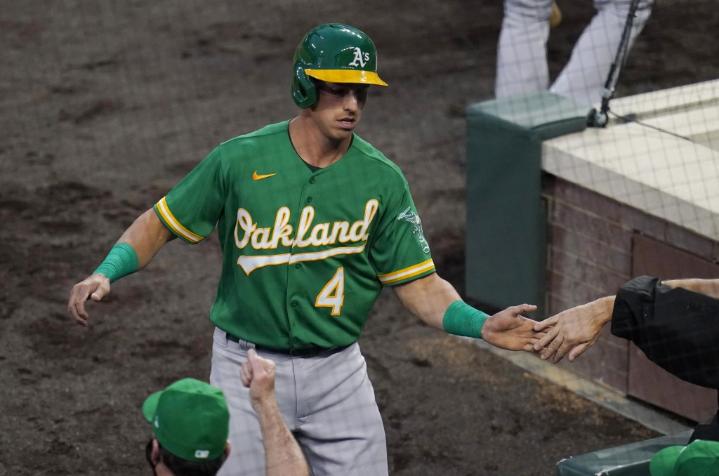 Oakland Athletics' Jake Lamb is congratulated after scoring against the Colorado Rockies during the second inning of a baseball game Tuesday, Sept. 15...
