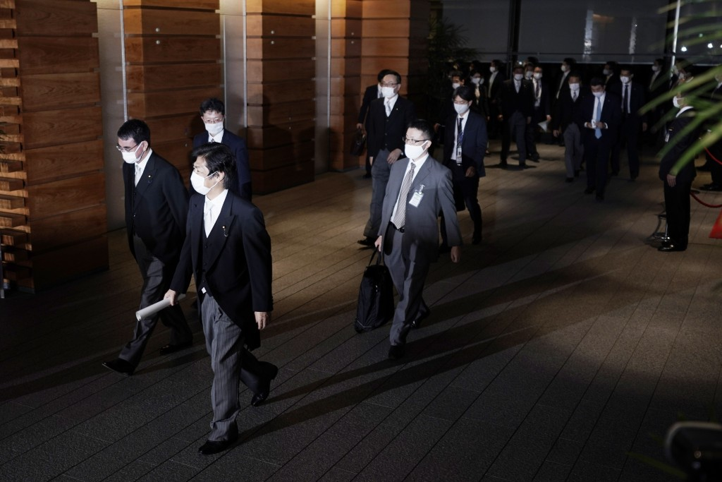 Newly appointed ministers, left,  are escorted by staffs as they leave the official residence for the Imperial Palace to attend the attestation ceremo...