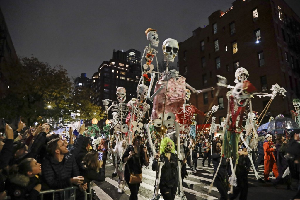 FILE - Revelers march during the Greenwich Village Halloween Parade in New York on Oct. 31, 2019. The holiday so many look forward to each year is goi...