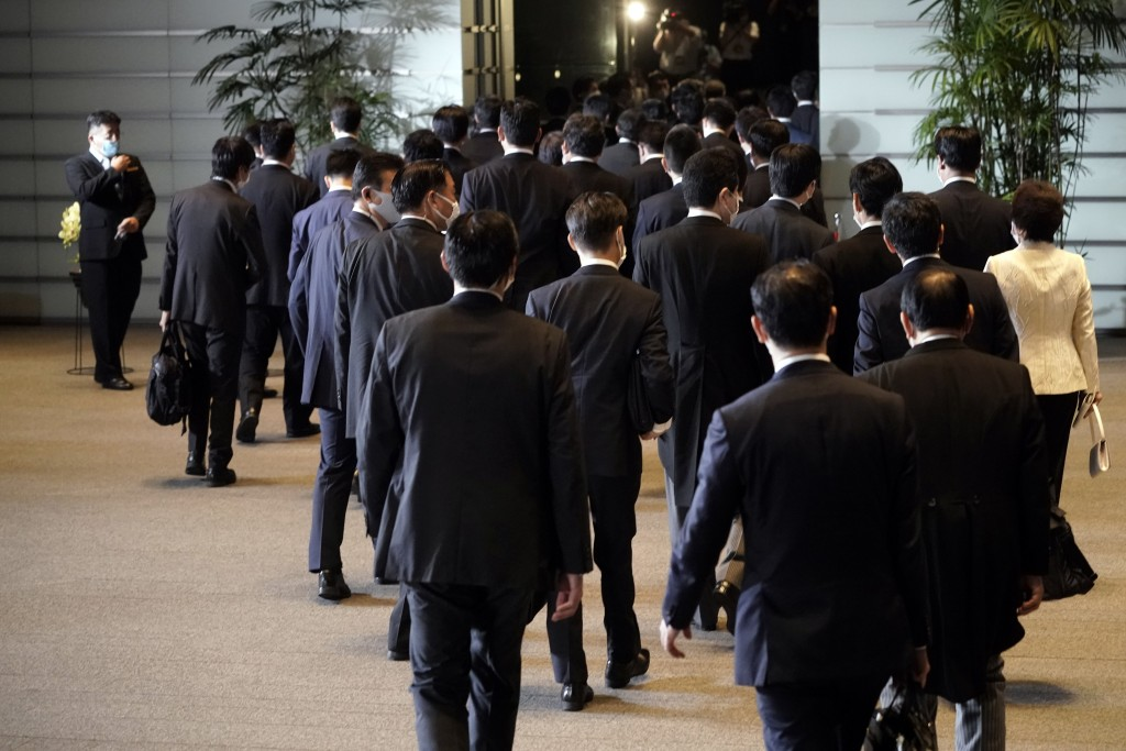 Newly appointed ministers are escorted by staffs as they leave the official residence of the prime minister, for the Imperial Palace to attend the att...