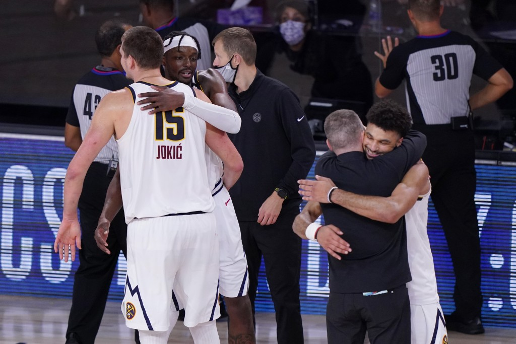 Denver Nuggets players and coaches celebrate their win over the Los Angeles Clippers in an NBA conference semifinal playoff basketball game Tuesday, S...