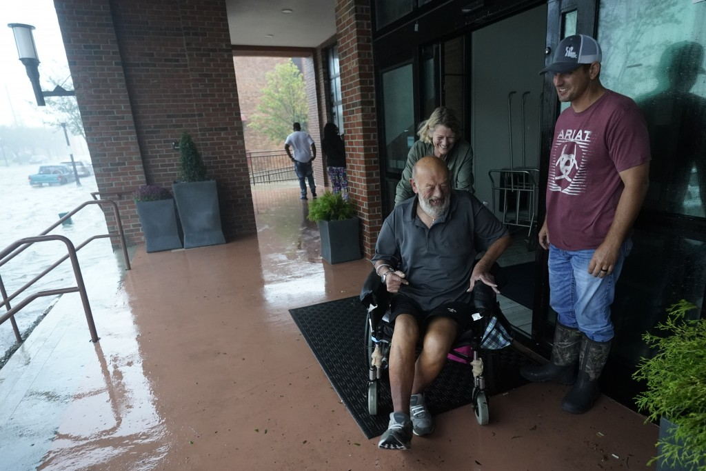 With flood water running through the streets people move outside a hotel for a view, Wednesday, Sept. 16, 2020, in Pensacola, Fla. Hurricane Sally mad...
