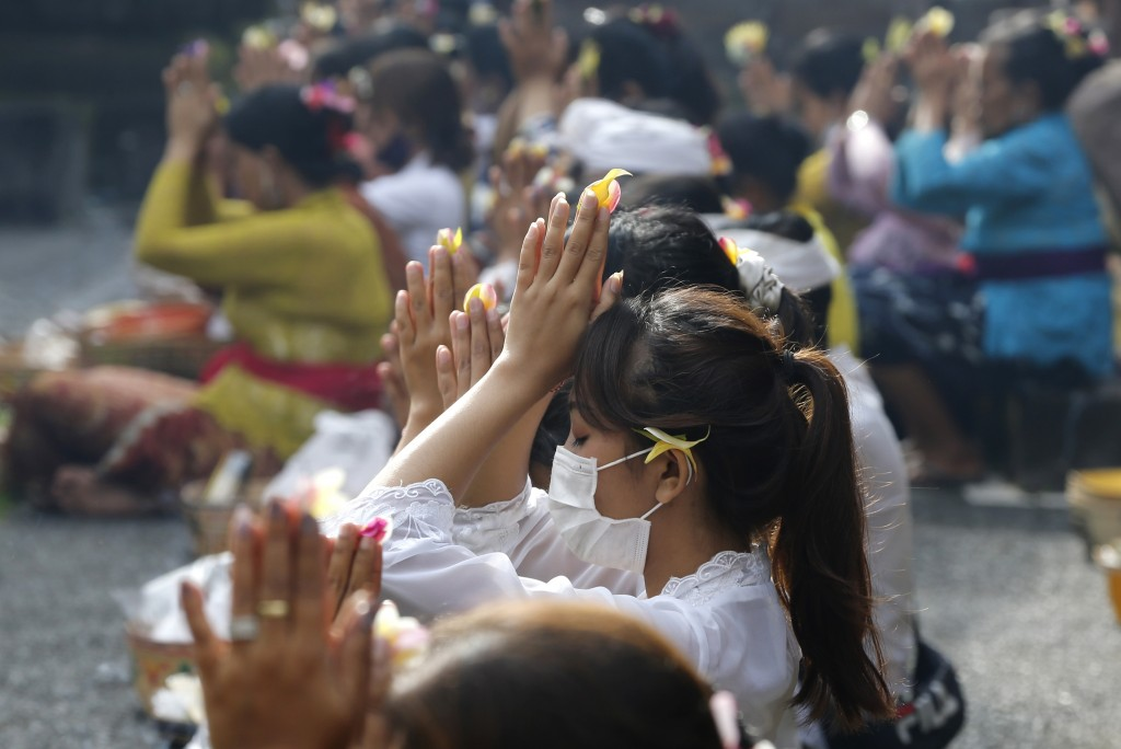 A woman wearing a face mask as a precaution against the new coronavirus outbreak during a Hindu ritual prayer at a temple in Bali, Indonesia on Wednes...