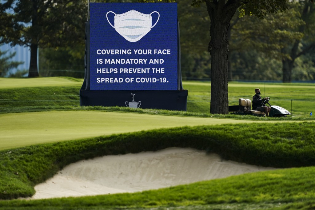 A sign urging COVID-19 prevention practices is displayed beside the 12th fairway during practice before the U.S. Open Championship golf tournament at ...